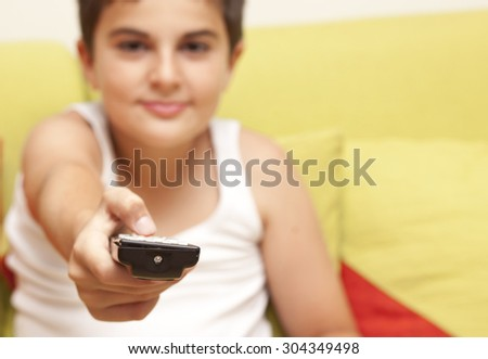 Young boy in living room with remote control  - stock photo