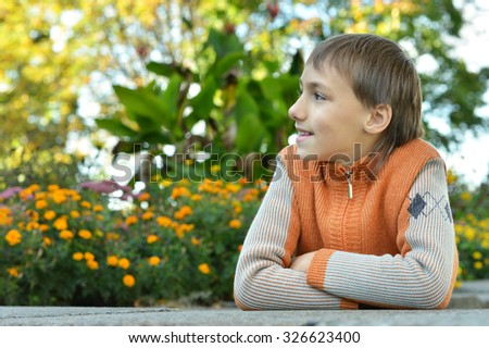 Young boy in park with flowers background