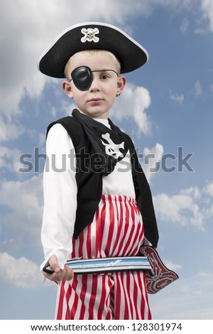 young boy in pirate costume outdoors against a clouds background - stock photo