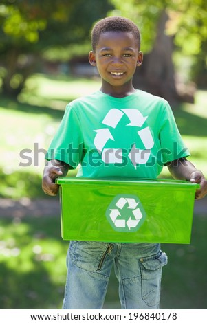 Young boy in recycling tshirt holding box on a sunny day - stock photo