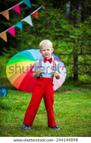 young boy in red pants and necktie outdoors - stock photo
