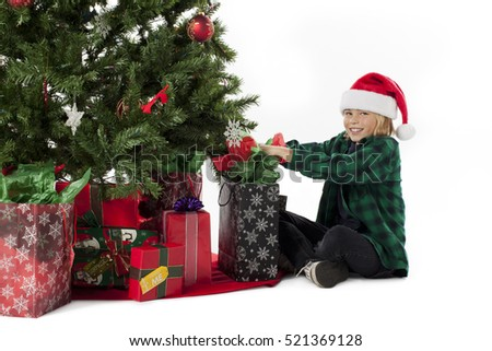 Young boy in santa claus hat hanging ornaments on a traditional christmas tree with a white isolated background