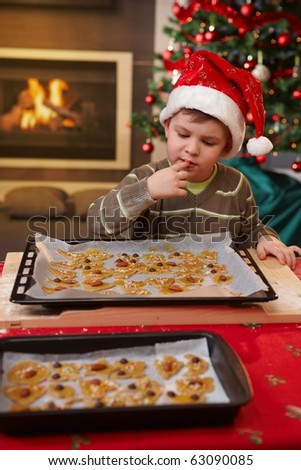 Young boy in santa claus hat tasting christmas cake at table.? - stock photo