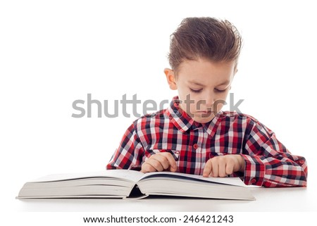 young boy in shirt reading from a big book