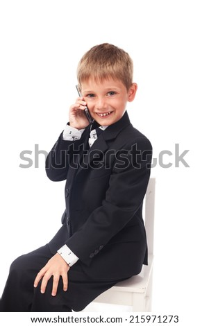 Young boy in the black suit  speaking by phone isolated on white