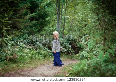 Young boy in the forest in a shirt