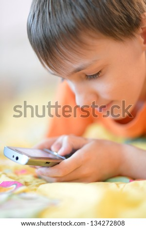 young boy in the orange shirt using mobile phone - stock photo