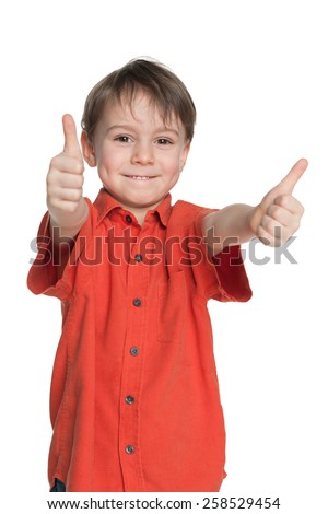 Young boy in the red shirt holds his thumbs up on the white background - stock photo