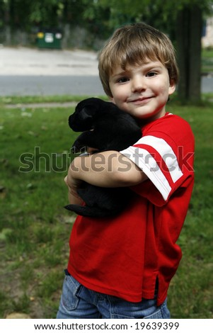 Young boy in the yard with his puppy.
