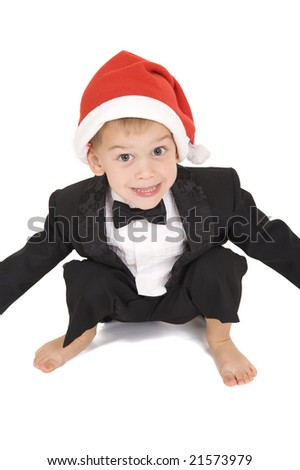 Young boy in tuxedo and santa hat squatting down. Isolated on white