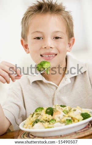Young boy indoors eating pasta with brocoli smiling - stock photo