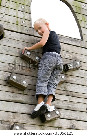 Young boy is climbing a wooden wall. - stock photo