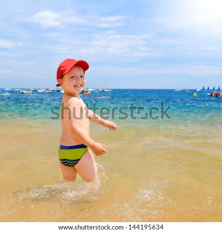 young boy is looking at camera in seaside