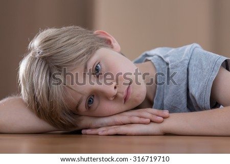 Young boy is sad because of his parents divorce - stock photo