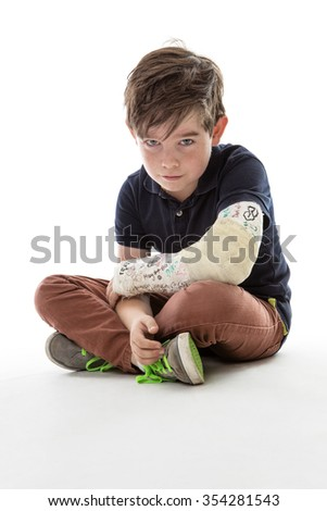 Young boy is sitting down and unable to join in because he has broken his arm