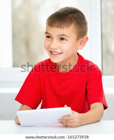 Young boy is using tablet while sitting at table, isolated over white - stock photo