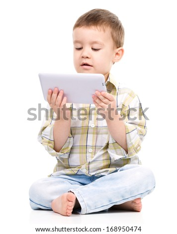 Young boy is using tablet while sitting on floor, isolated over white - stock photo
