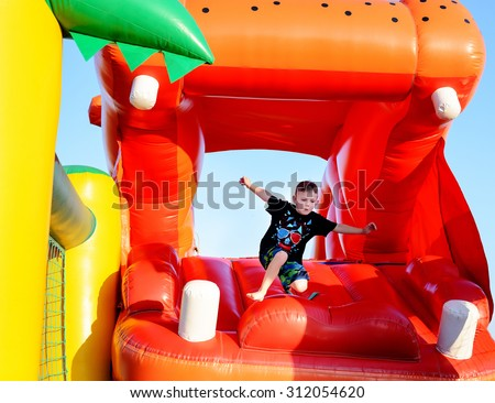 Young boy jumping barefoot on a plastic jumping castle with his arms in the air as he enjoys a summer day at a playground or fair - stock photo