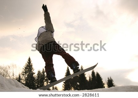 Young boy jumping high on a snowboard.