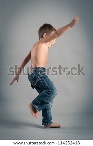 Young boy jumping. Studio portrait with grey background. - stock photo