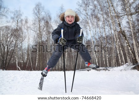 Young boy jumps and spreads legs on cross-country skis inside winter forest at sunny day - stock photo