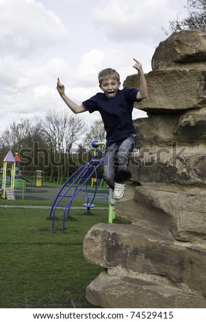 young boy jumps from a climbing wall