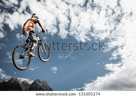 young boy jumps high with his bike in front of mountains and sky - stock photo