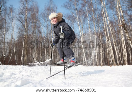 Young boy jumps sideways with cross-country skis and poles inside winter forest at sunny day - stock photo