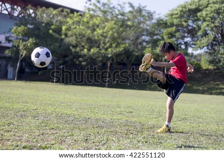 young boy kick soccer ball in green grass field, kid athlete with jersey training football in sunny outdoor park - stock photo