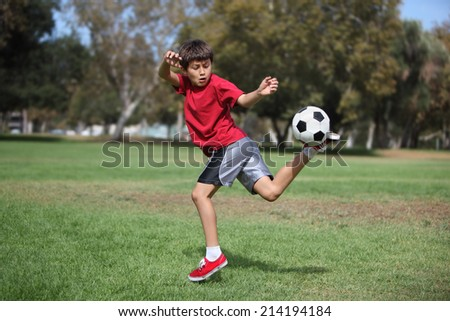 Young boy kicks a soccer ball in the park - Authentic action - stock photo