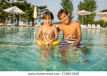 Young boy kid child splashing in swimming pool having fun leisure activity