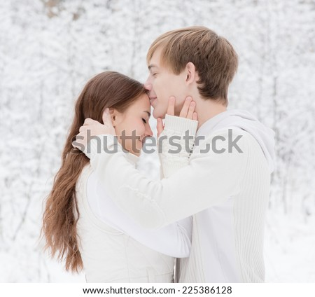 Young boy kisses a girl in forehead - stock photo