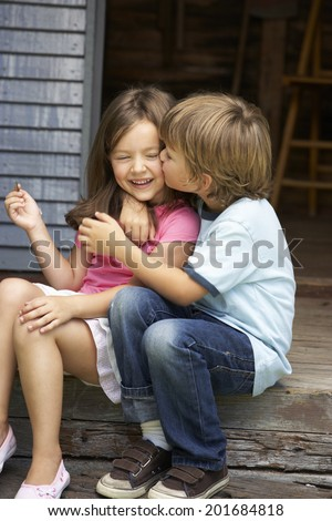 Young boy kissing sister on veranda - stock photo