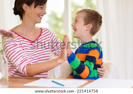 Young boy laughing with his mother or teacher and clapping hands as they sit together at a table or desk - stock photo