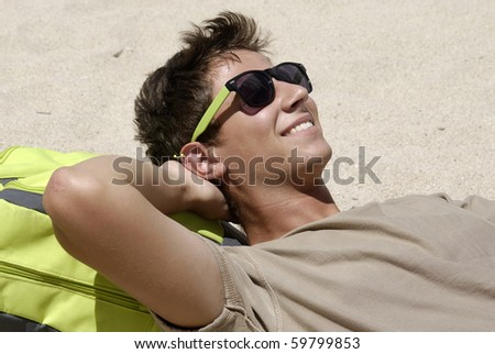 Young boy laying in the beach with cellphone