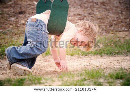 Young boy laying on a swing - stock photo