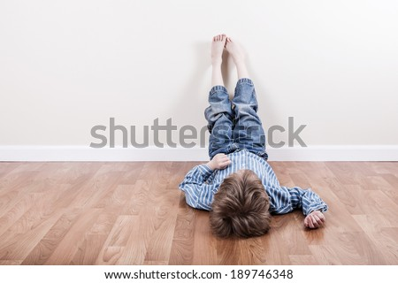 Young boy laying on the floor - stock photo