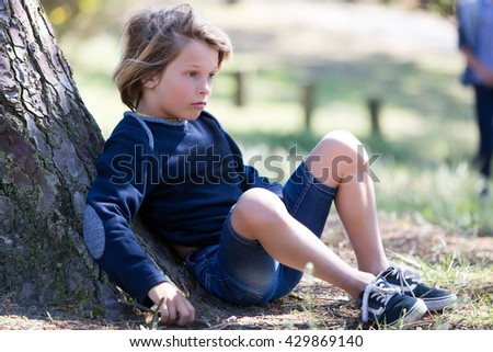 Young boy laying out in park