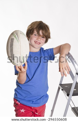 Young boy leaning a ladder and holding a rugby league ball in the air while smiling at the camera. - stock photo