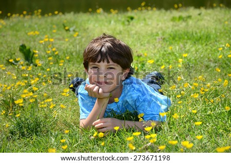 young boy leaning chin in hand laying down in grass outside - stock photo