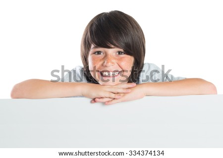 Young boy leans over poster. Happy cute kid leaning on blank white poster. Closeup of smiling boy leaning on empty grey placard and looking at camera isolated on white background. - stock photo