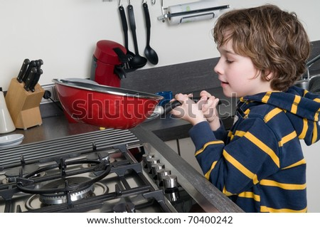 Young boy learning to cook in a modern kitchen