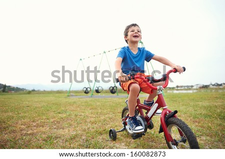 Young boy learning to ride a bike with bicycle training wheels in park