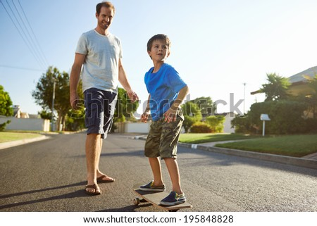 young boy learning to ride skateboard as father teaches him in the suburb street having fun. - stock photo