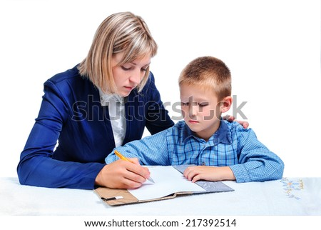 young boy learning to write under the supervision of the mother - stock photo