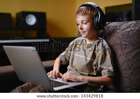 Young boy listening to music and browsing the wireless internet - stock photo