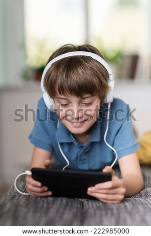 Young boy listening to music or an e-learning class lying on his stomach on a couch at home wearing headphones attached to his tablet - stock photo