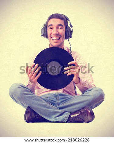 young boy listening to music, sitting and holding a vinyl - stock photo