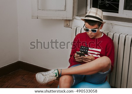 young boy listening to music with mobile phone