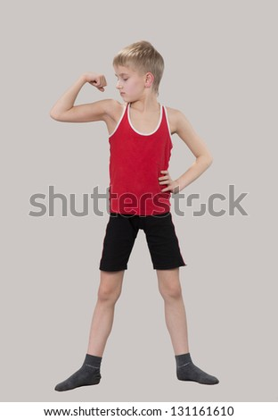 Young boy looking at his muscles - stock photo